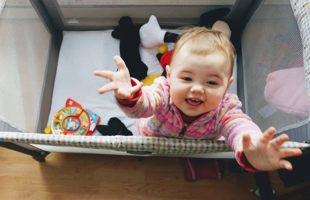 Baby girl reaches up from pack n play.
