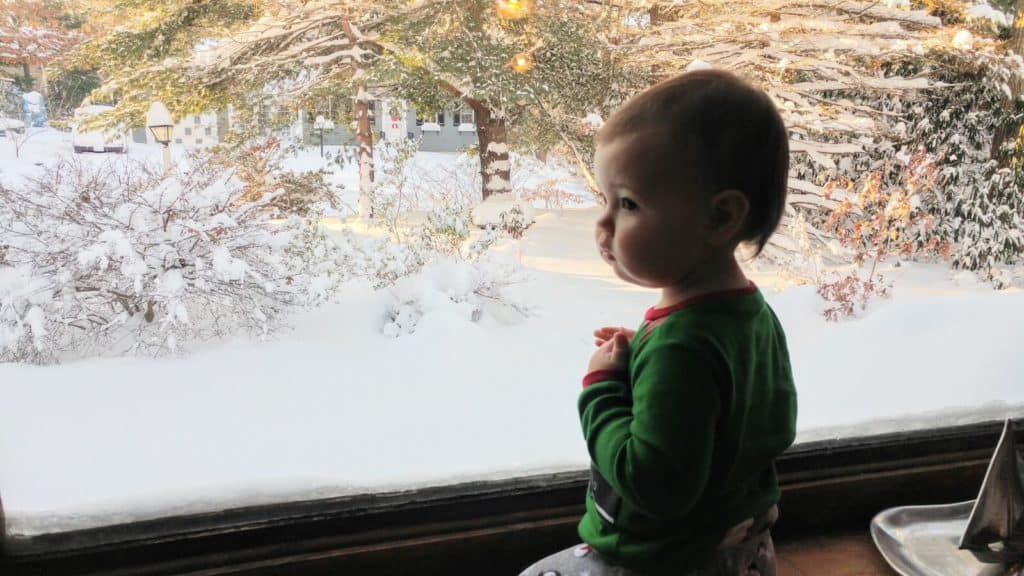 Baby girl sits in window.