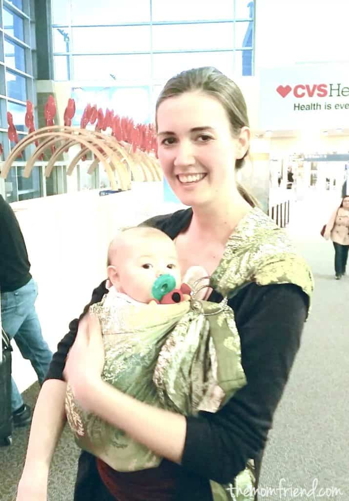 Mother holds baby in baby sling at airport.