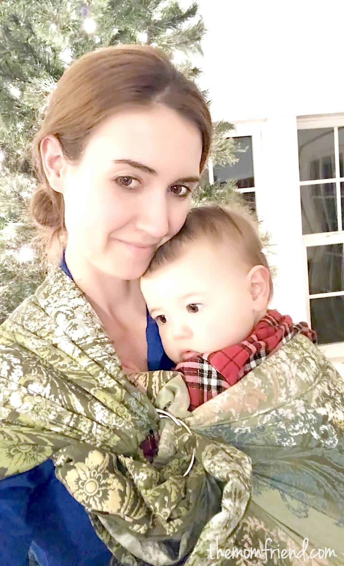 Woman holds baby in baby sling.