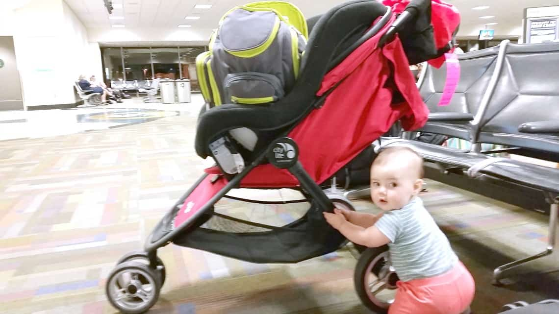 Baby girl holds onto side of stroller at airport.