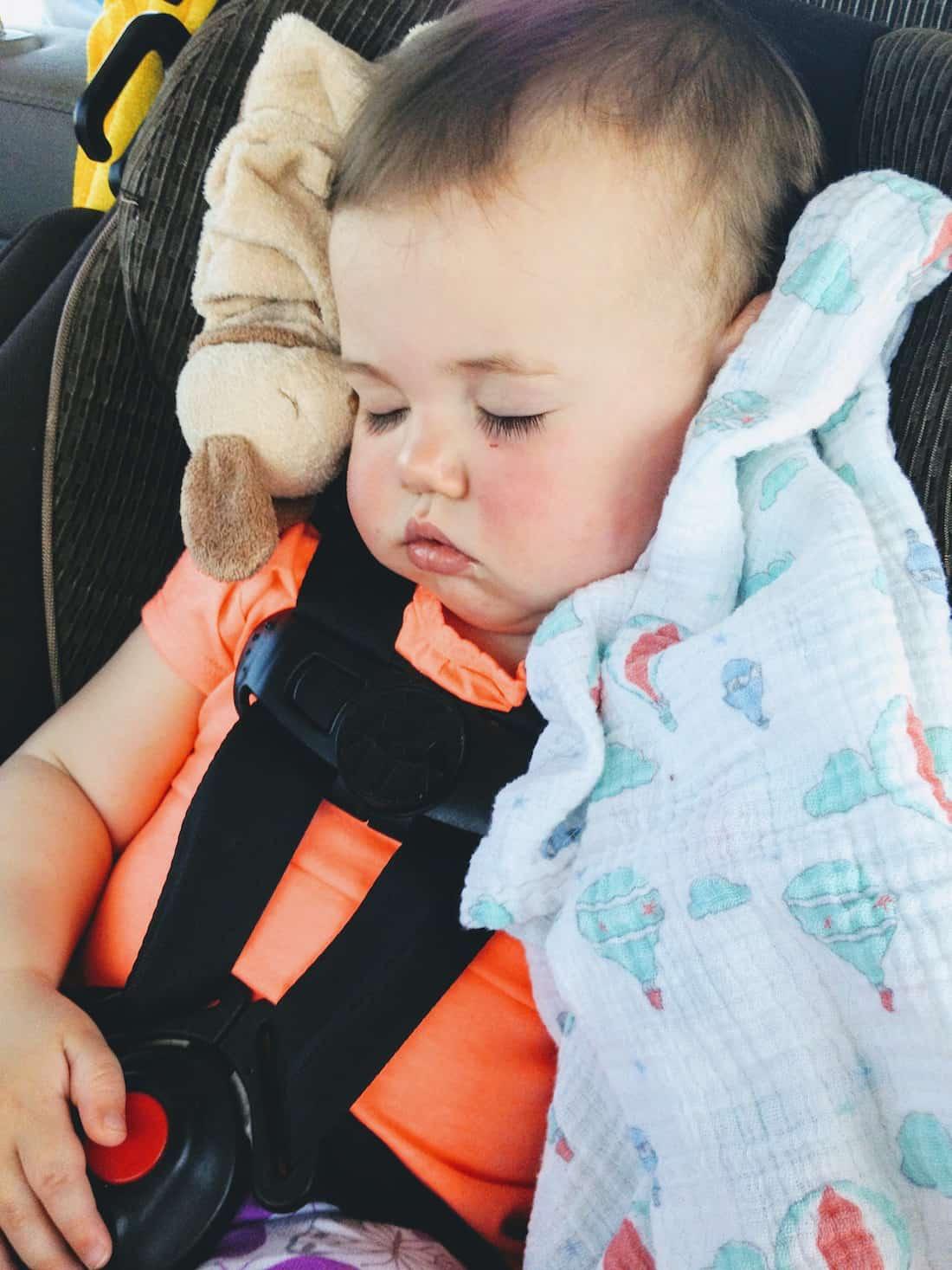 Little girl sleeps in car seat.