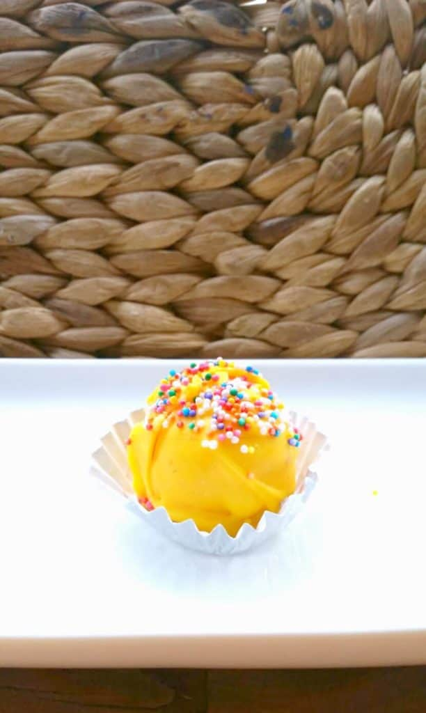 yellow cake pop on a plate for a gender reveal party