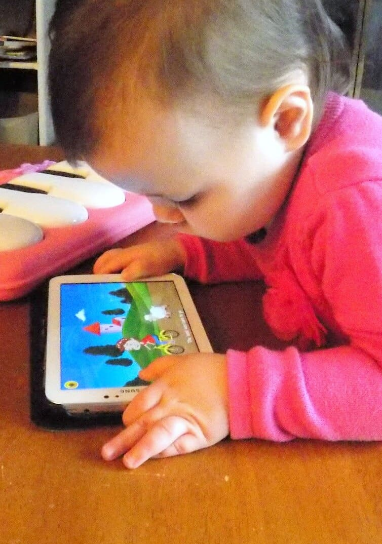 Little girl watches show on tablet.