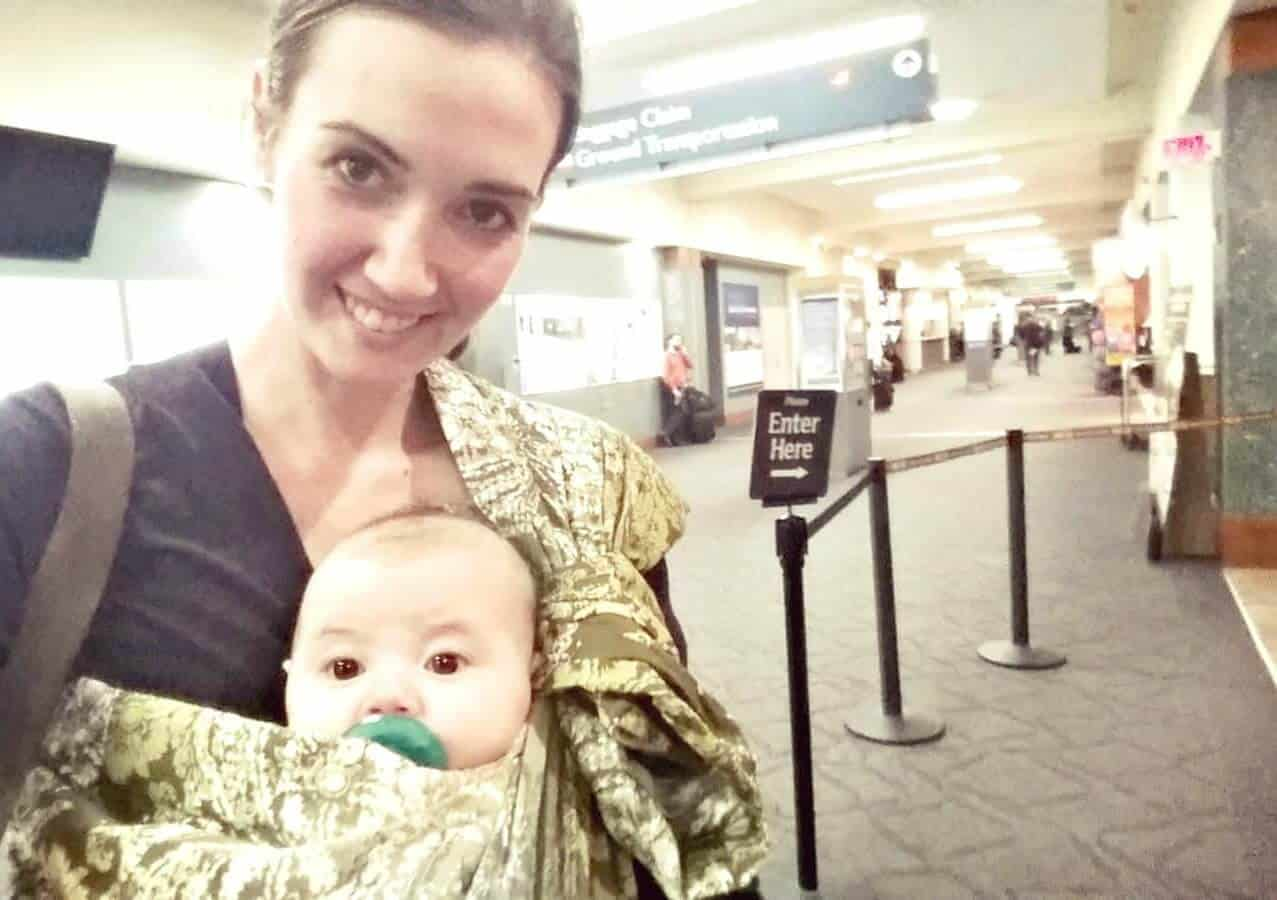 Mother holds baby using sling in airport.