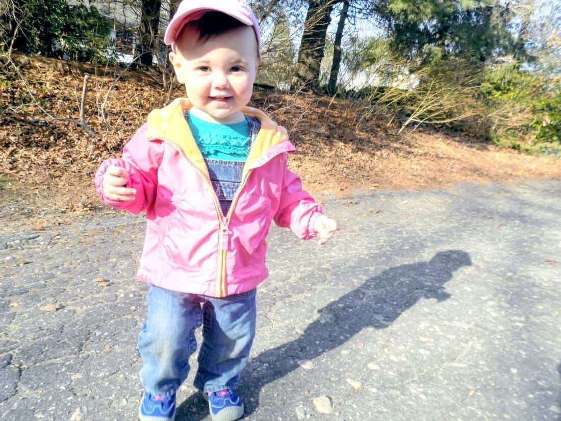 Little girl plays outside in pink jacket.