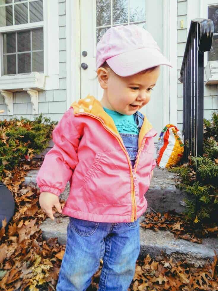 Baby girl plays outside in front of doorsteps.