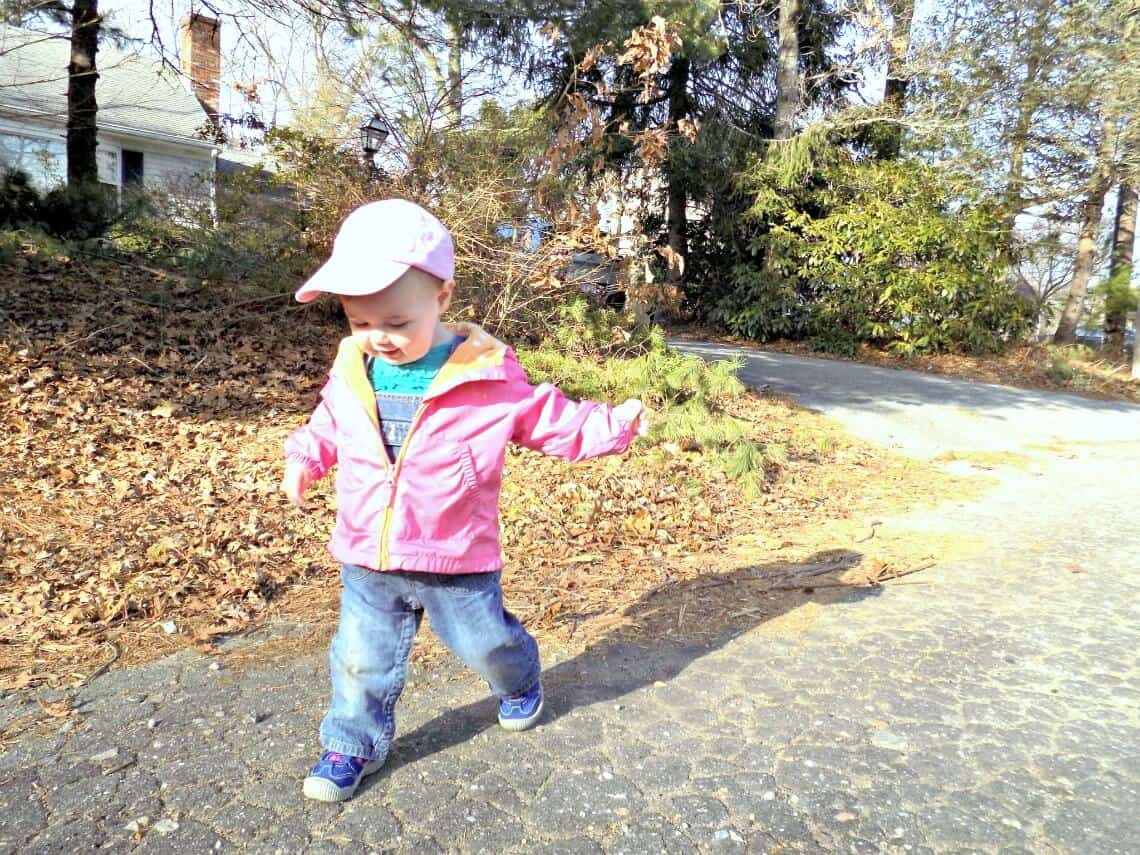 Toddler girl plays outside for spring.