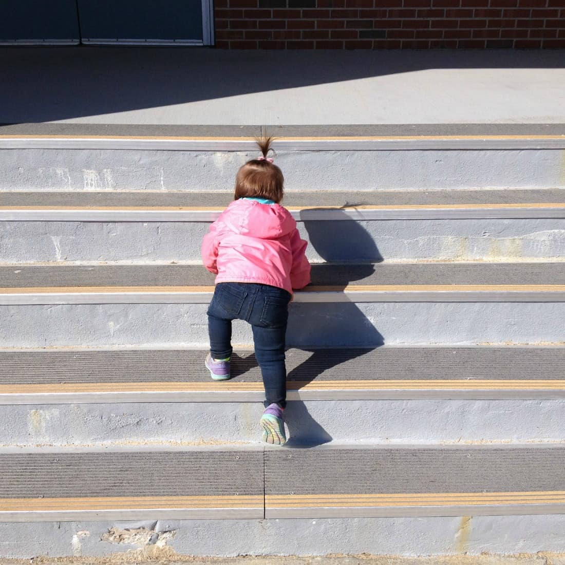 Toddler girl climb stairs outside.