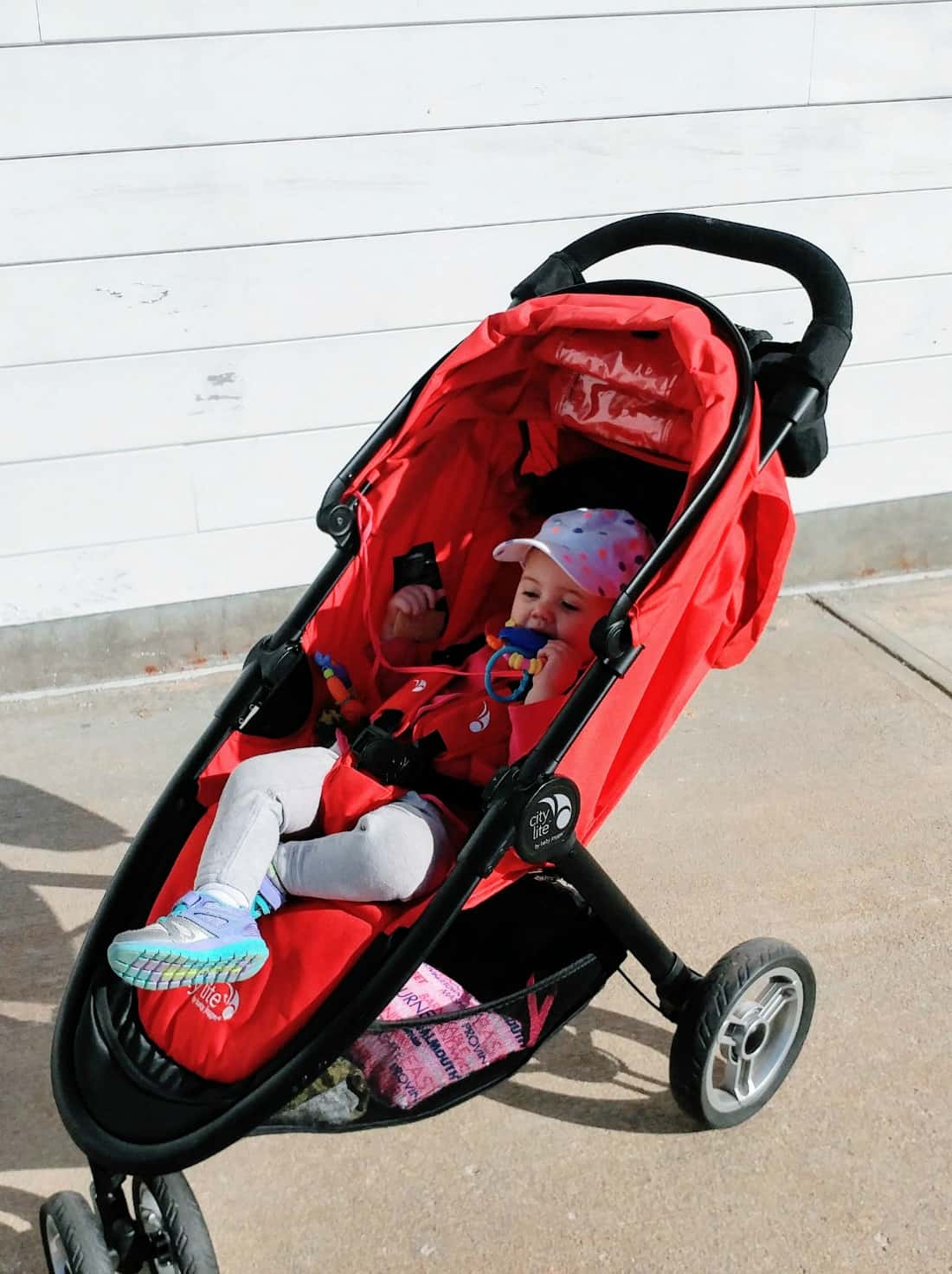Baby girl plays in red stroller.