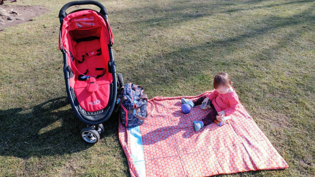 Baby girl sits on picnic blanket next to jogging stroller.