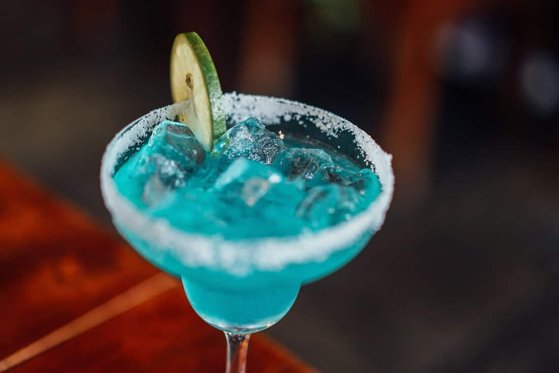 Blue margarita with slice of lime.