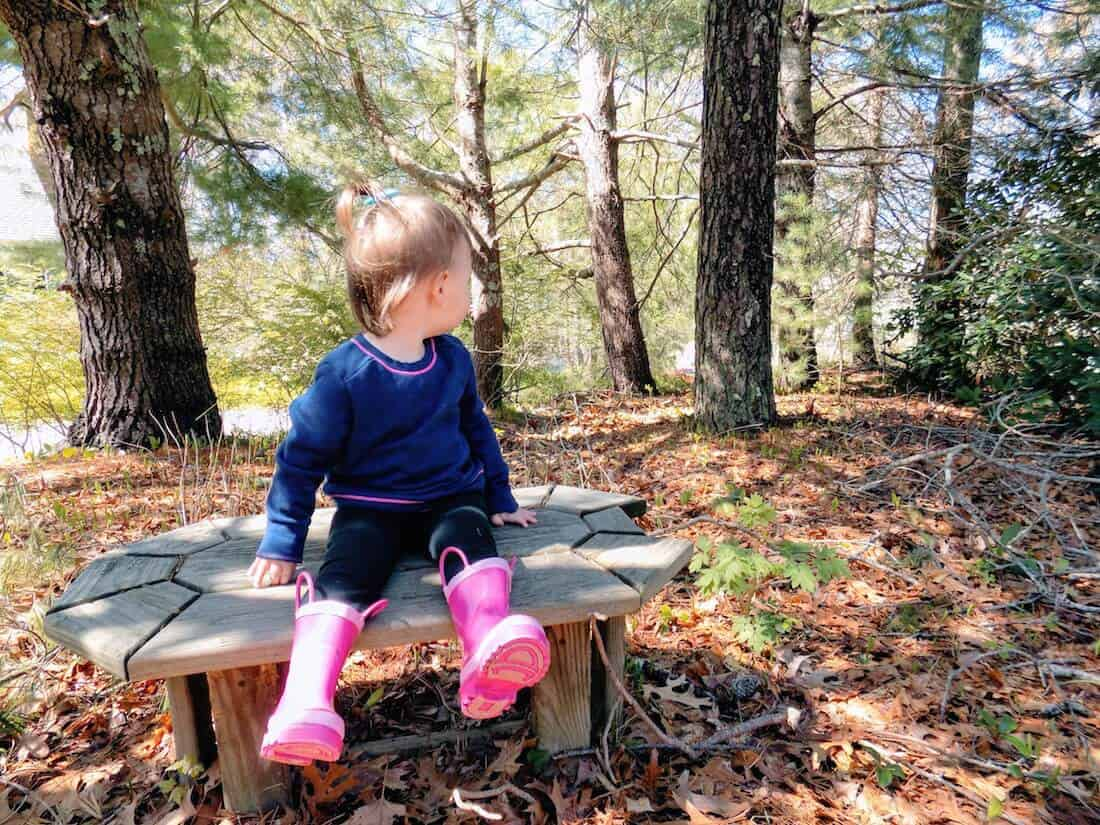 Toddler girl plays in wooden area.