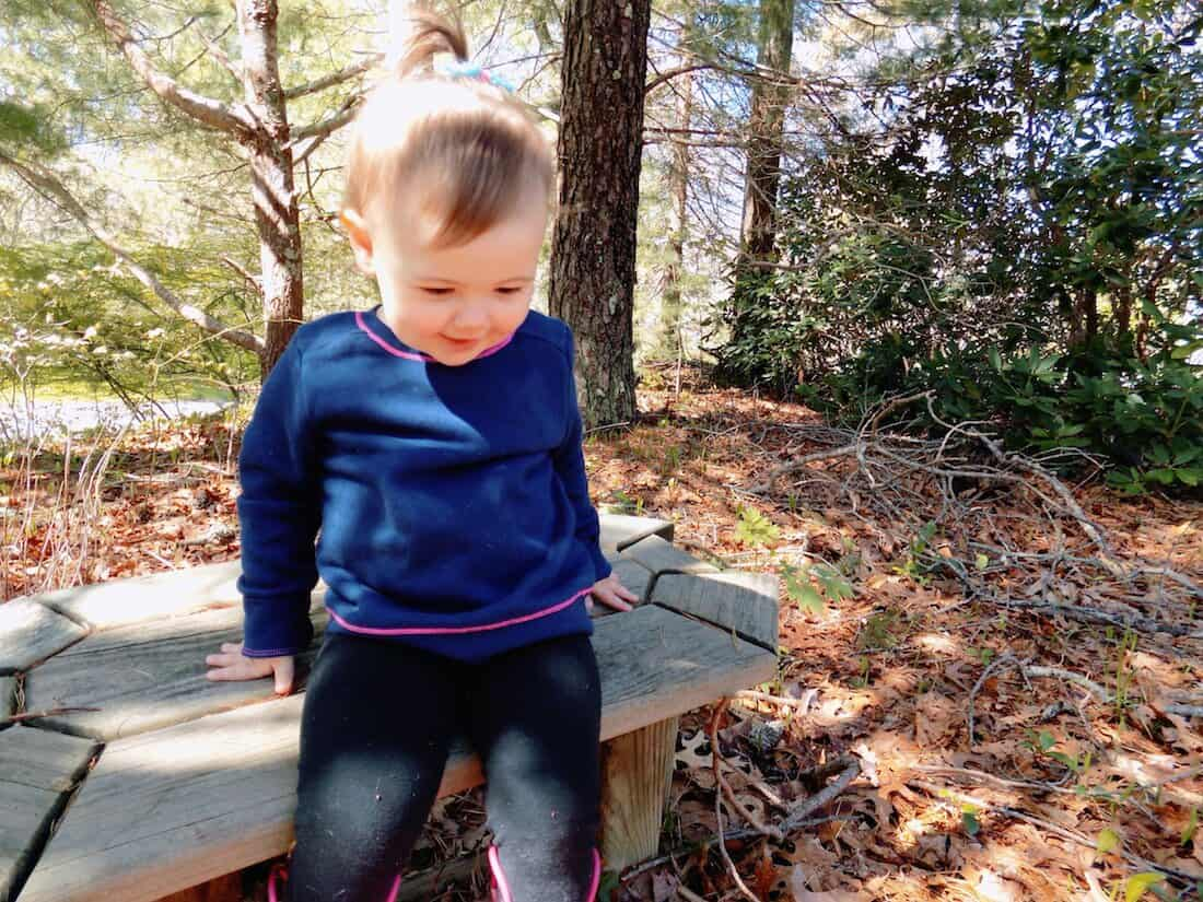 Little girl stands up from outdoor bench.