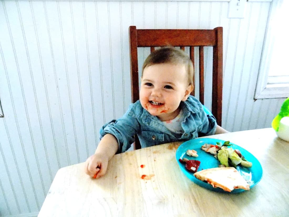 Toddler girl eats pizza at dining table.