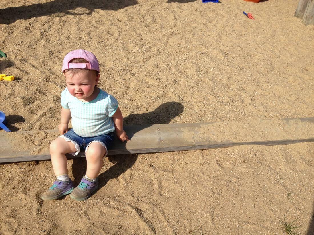 Toddler girl sits on log over sand.