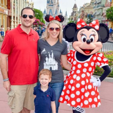 Family poses with Mini Mouse at Disneyland.