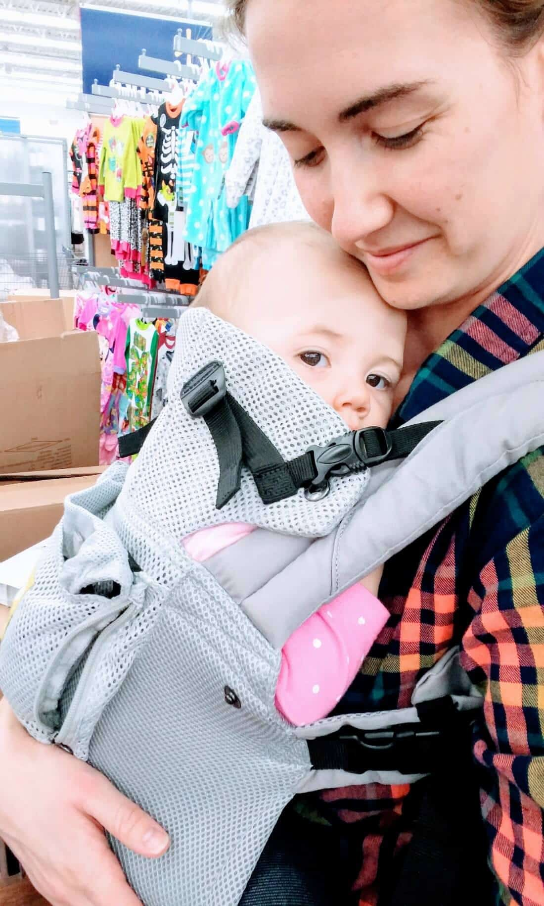 Mom wears baby at store using baby carrier.