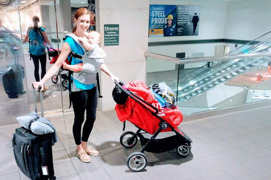 Mom wears baby in carrier at store.