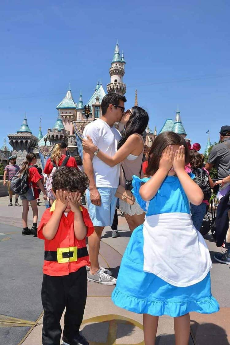Parents kiss in front of Disney castle while children cover their eyes.