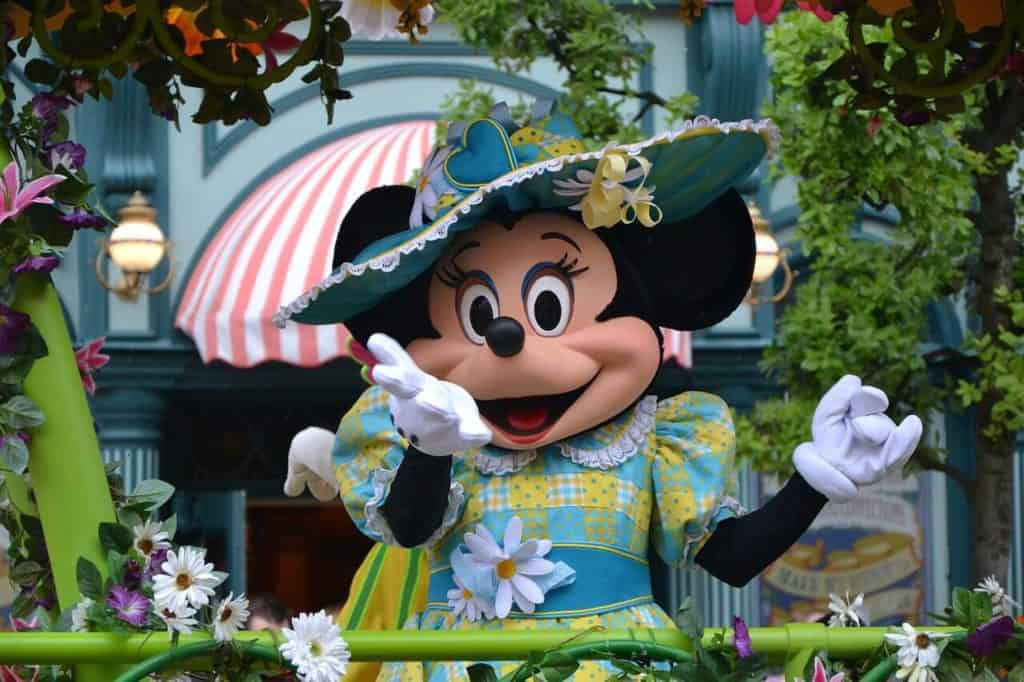 Mini mouse waves to crowd at Disney.