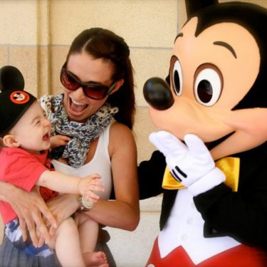Mom introduces little girl to Mickey Mouse at Disneyland.