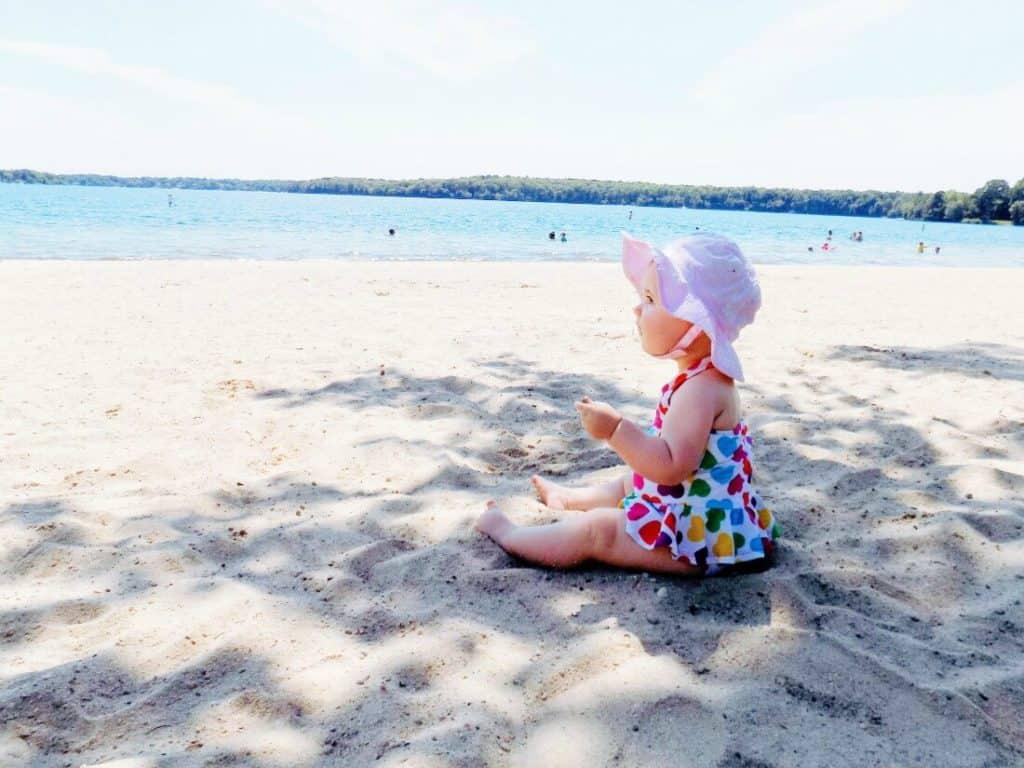 Baby girl sits on beach.