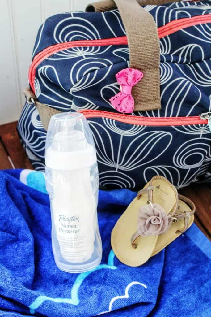 Beach bag and baby bottle next to flip flops.