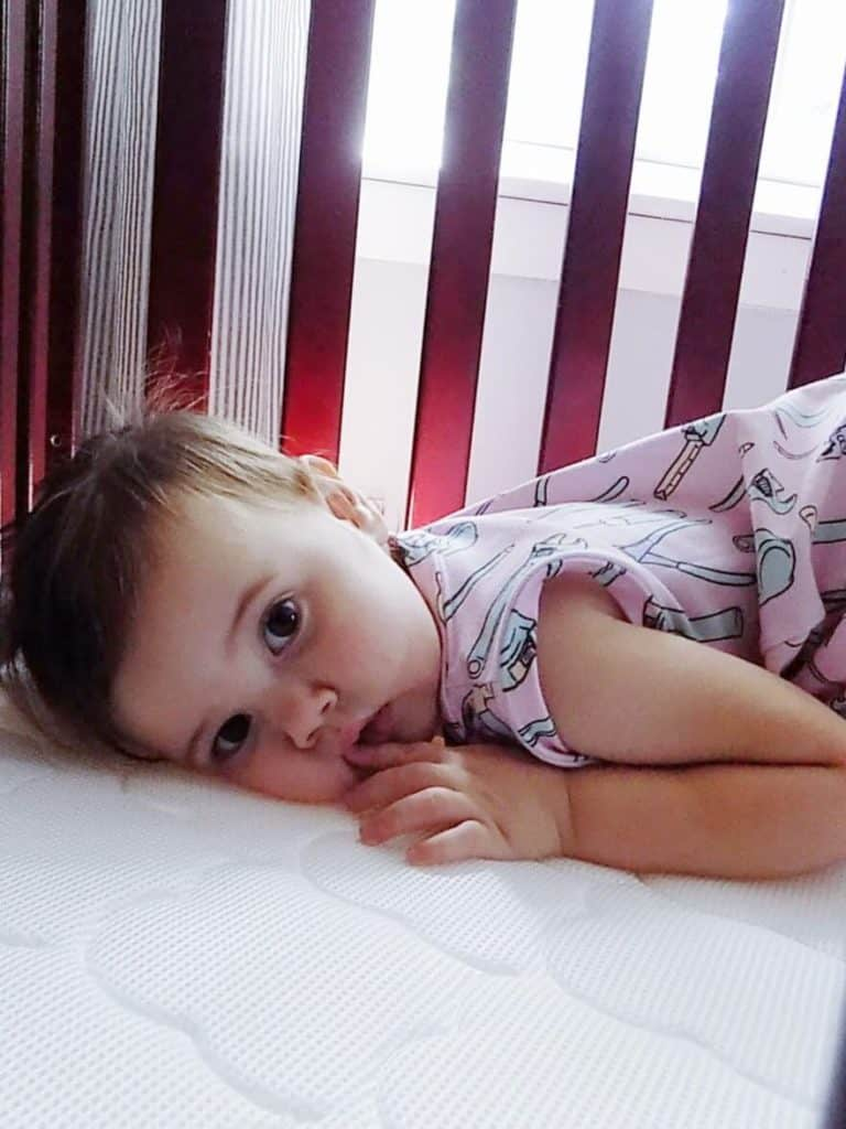 Toddler girl lays in crib and stares at camera.
