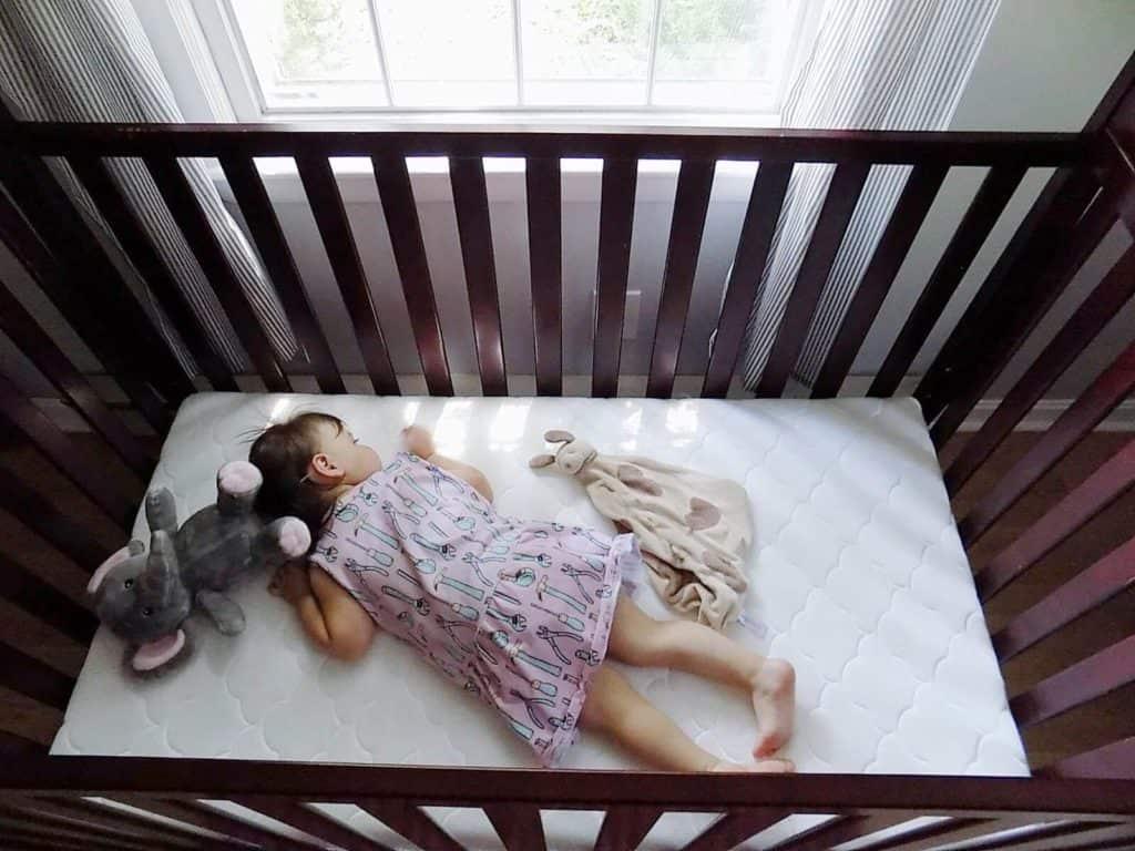 Toddler girl sleeps in crib.