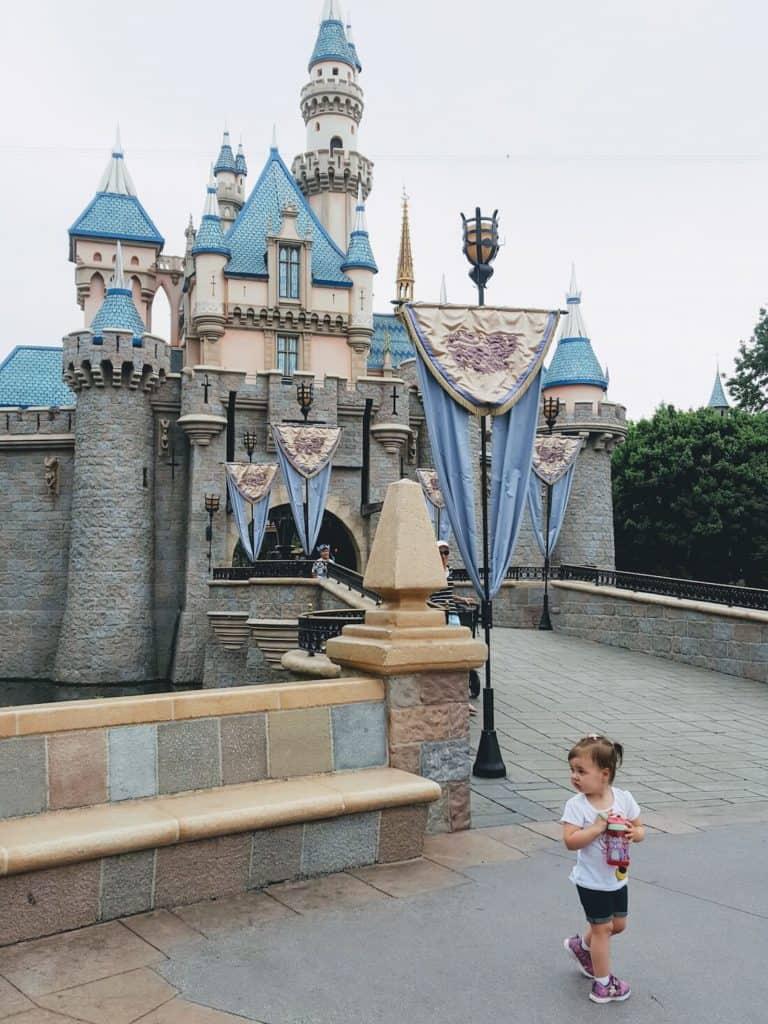 Toddler girl walks in front of Disney Castle.