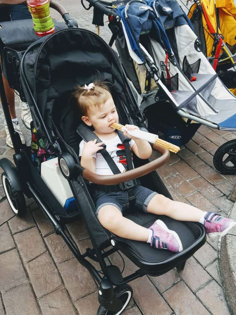 Little girl eats treat at Disney.
