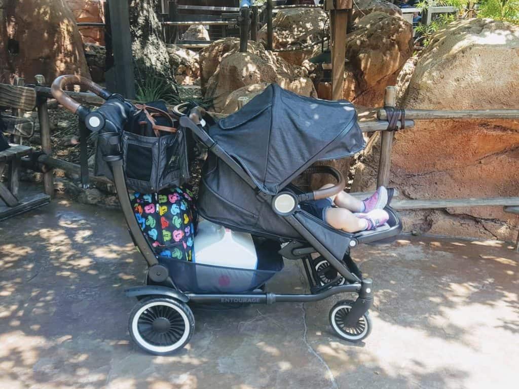 Girl sits in Austlen Entourage stroller at Disney park.