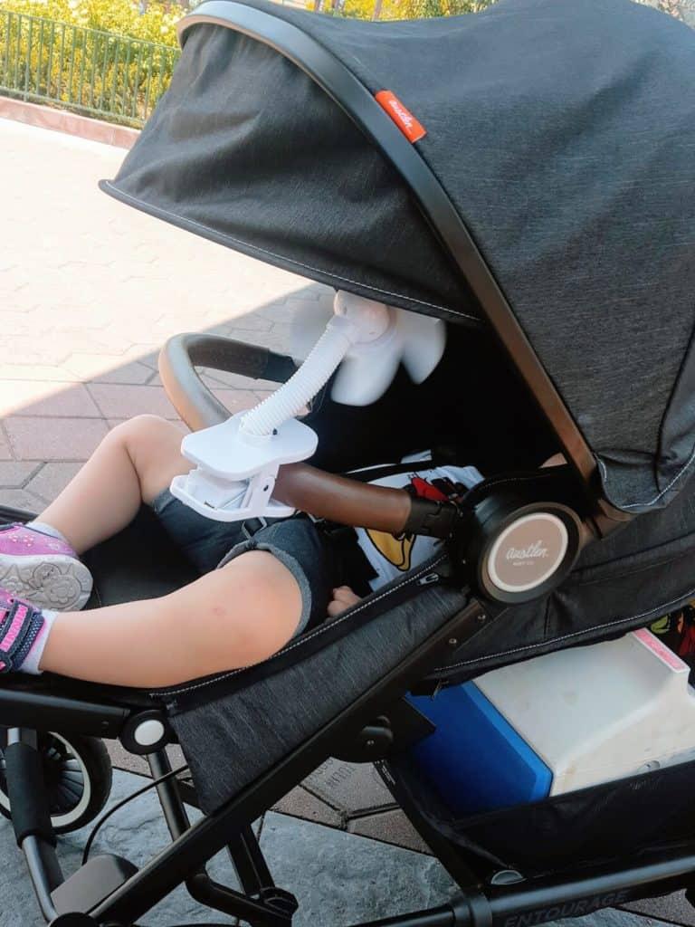 Toddler girl reclines in Entourage stroller at Disney World.