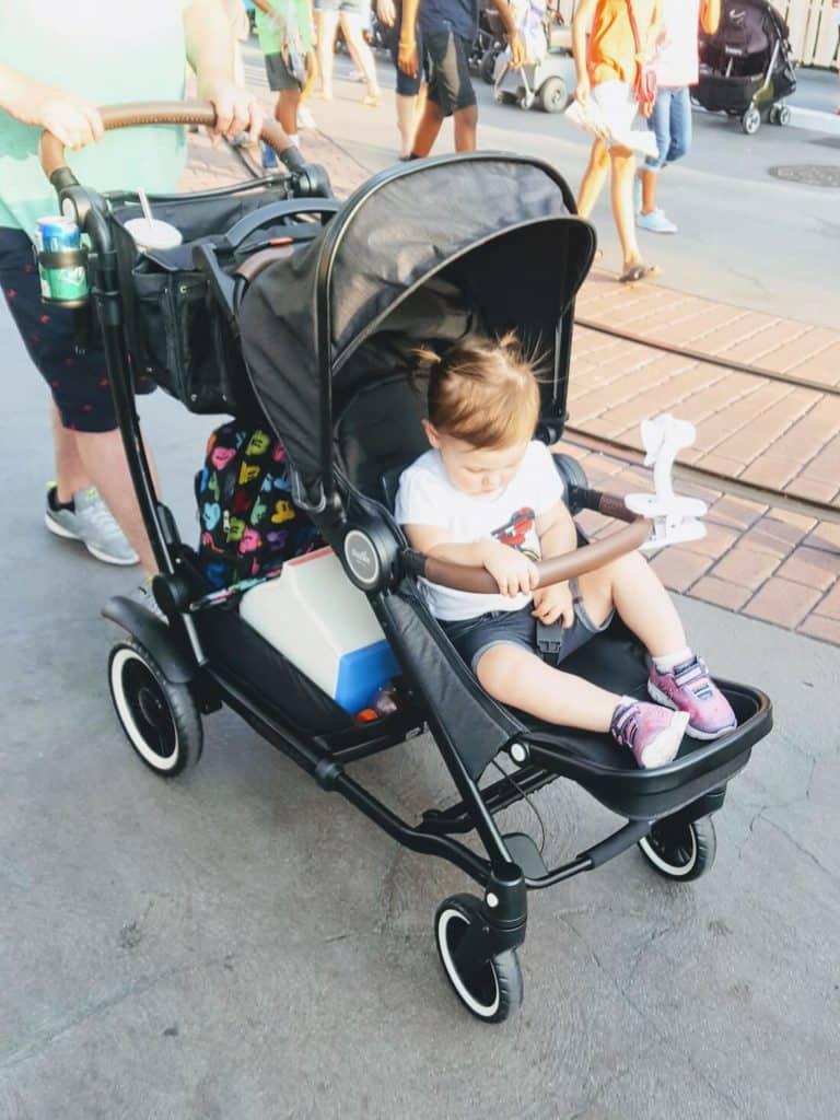 Little girl is pushed in stroller at Disney park.