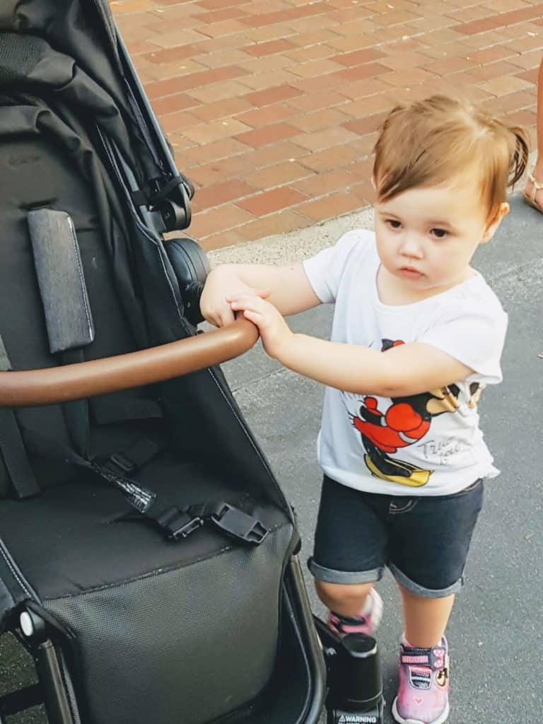 Toddler girl stands next to Austlen stroller at Disney.