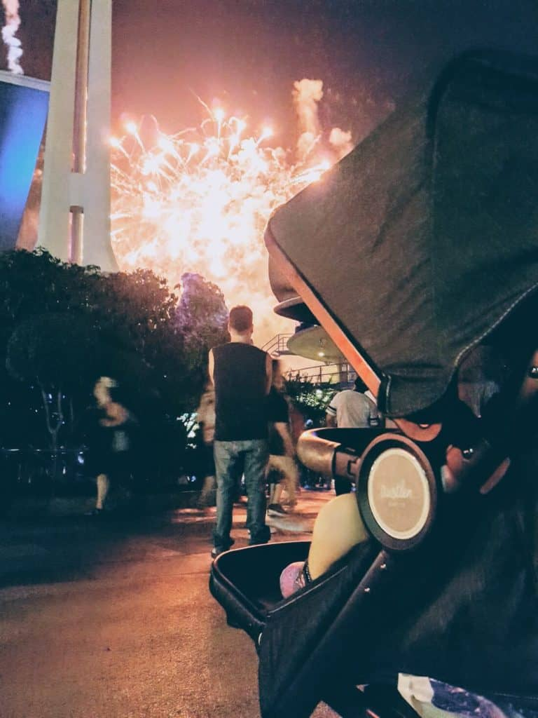 Toddler girl watches fire works from stroller at Disney park.