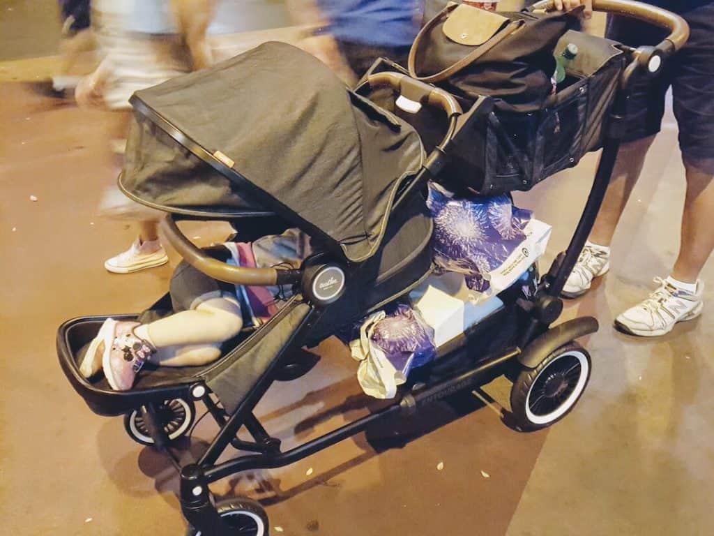 Stroller full of toddler supplies and sleeping toddler.