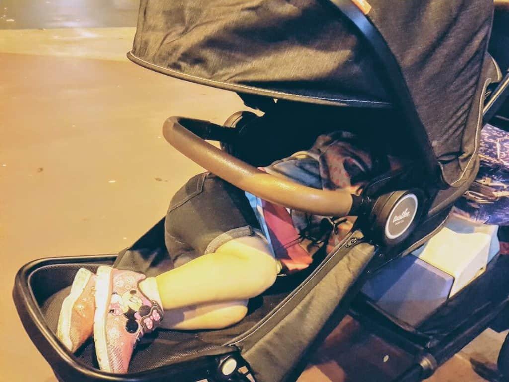 Little girls sleeps in stroller.