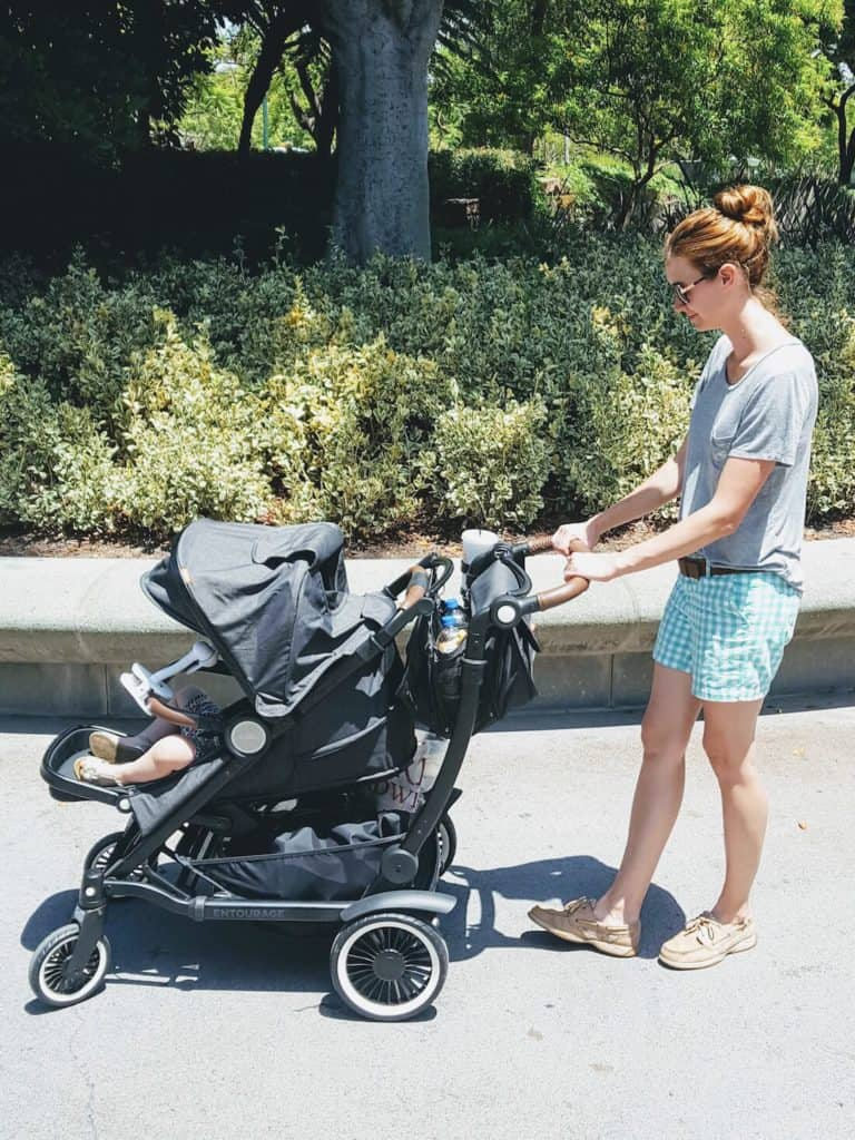 Mom pushes child in stroller down paved path.