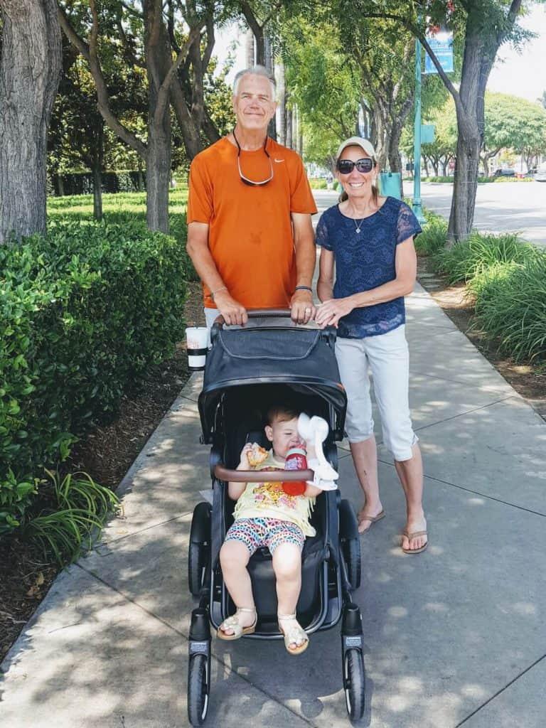 Grandparents push toddler in stroller down paved lane.