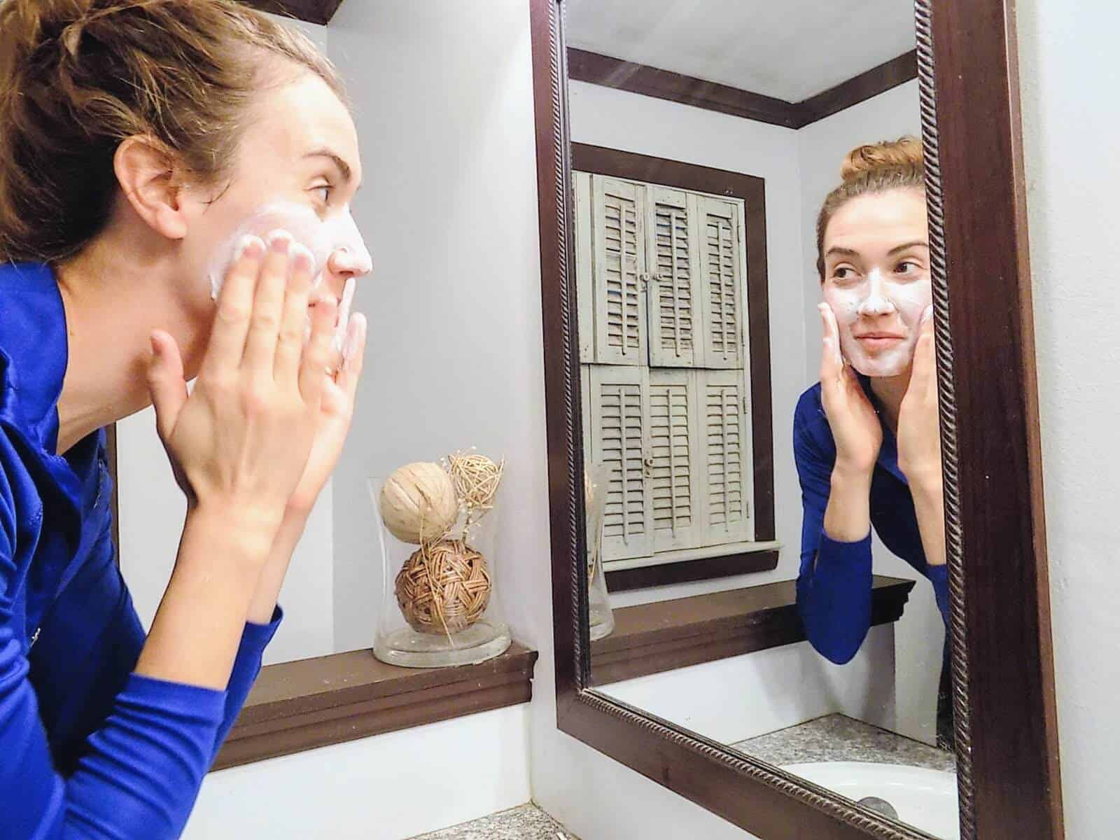 Woman washes face in mirror.