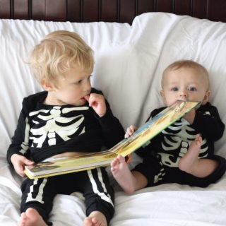 Baby and toddler read book in skeleton Halloween costumes.