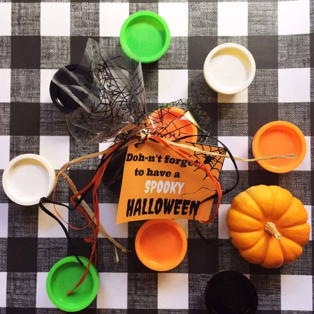 Halloween activity with play dough and pumpkins on checkered tablecloth.