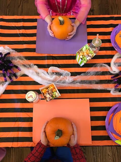Children participate in fun Halloween ideas at table.