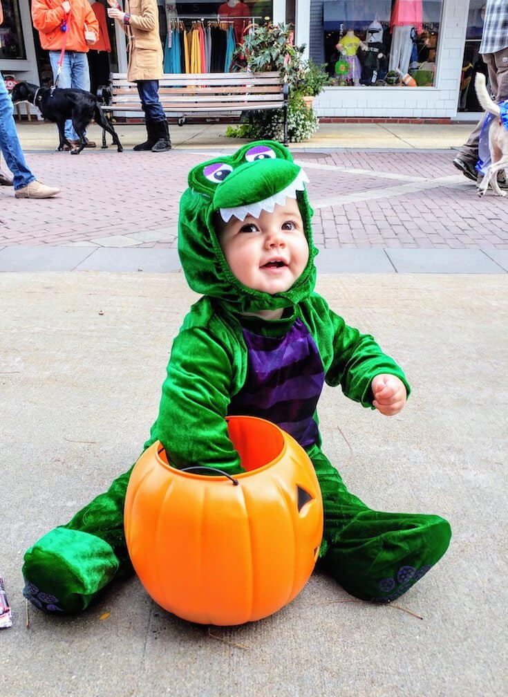 Baby in dragon costume reaches into plastic pumpkin.