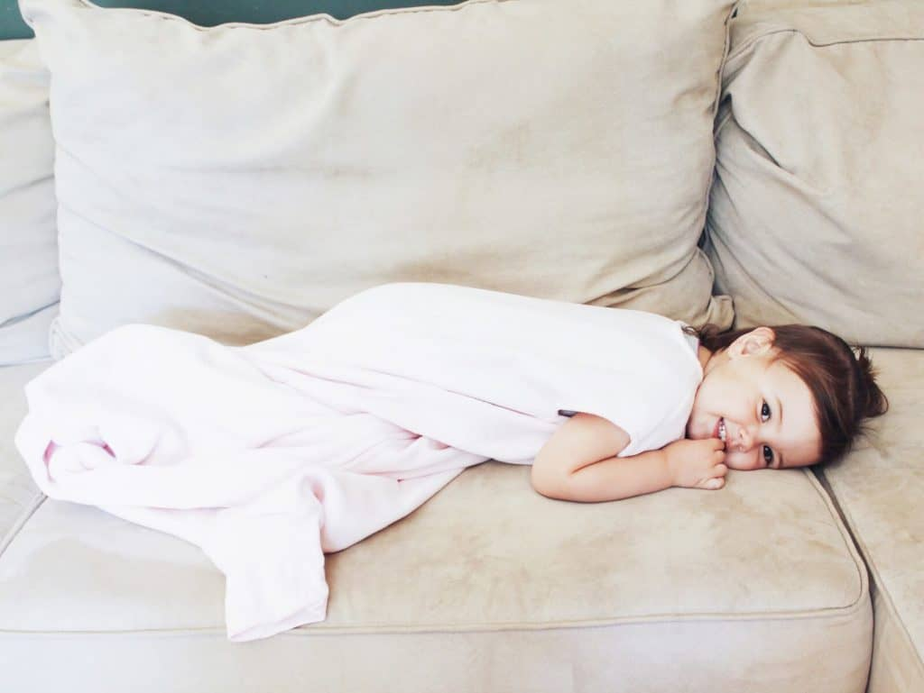 Toddler girl lays on couch.