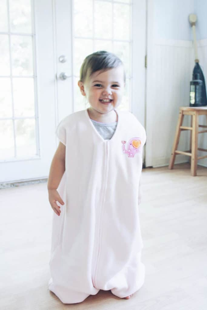 Toddler girl wears sleep sack.