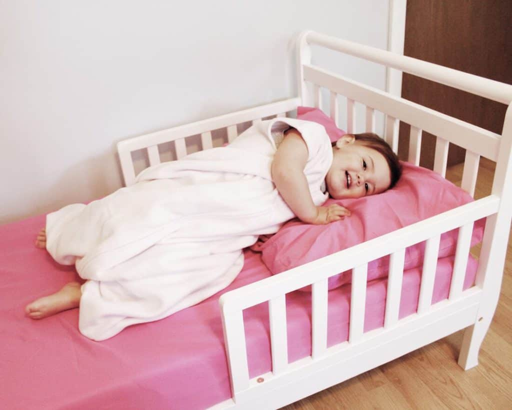 Toddler girl in sleep sack lays in bed.