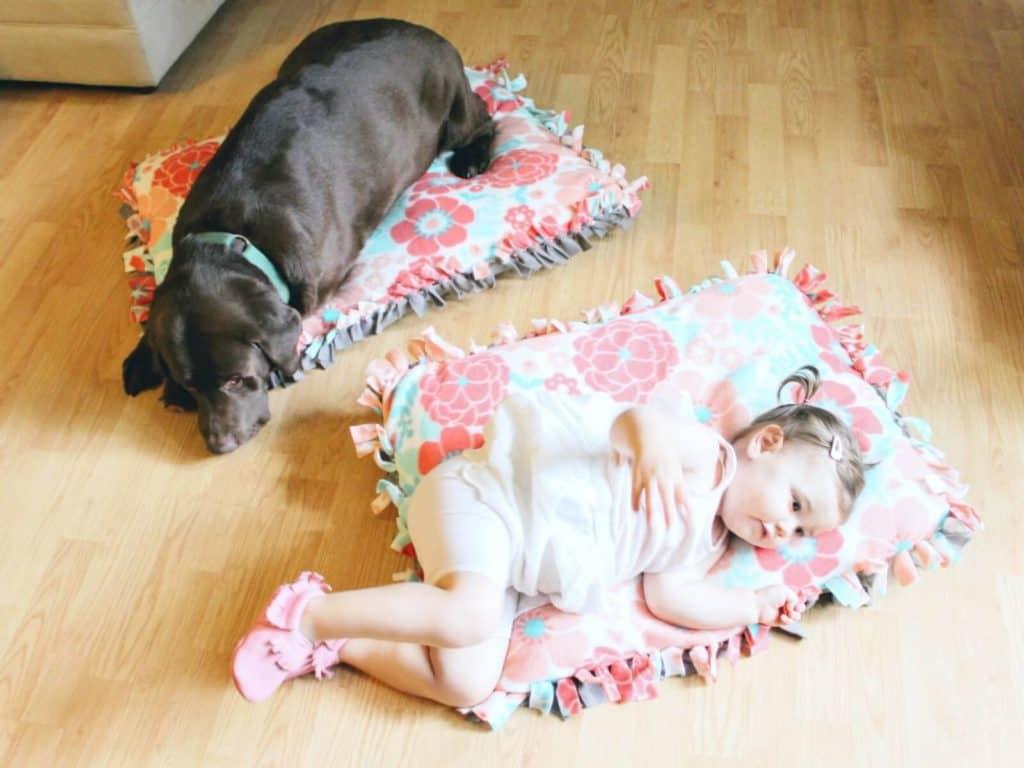 Dog and little girl sleep on pillows on the floor.